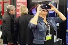 Am Stand von imsimity: Die Samsung Gear VR und im Hintergrund der 3D-Fernseher mit dem Cyberclassroom