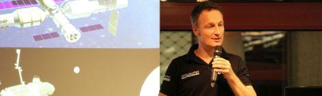 ESA-Astronaut Matthias Maurer hält einen Vortrag. Im Hintergrund sieht man auf seinen Vortragsfolien Raumstationen im Erdorbit und im Mondorbit.