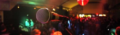 Leicht verschwommen im Hintergrund: Eine Halle voll von Partygästen. Verschiedenfarbige Scheinwerfer an der Decke. Im Vordergrund ein Mikrofonständer mit Mikrofon.