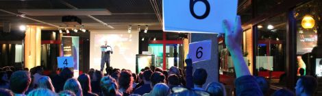 Eine der Wertungsphasen des Science Slams. Im Vordergrund die blau beleuchteten Hinterköpfe des Publikums. Drei Personen aus dem sichtbaren Publikum halten Wertungskarten hoch. Auf der Bühne notiert der Moderator die Wertungen.