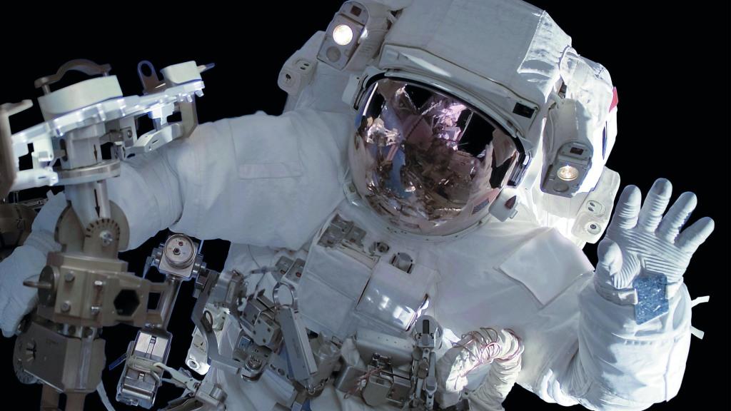 Ein Mensch im Raumanzug winkt bei einem Außenbordeinsatz im Weltall in die Kamera