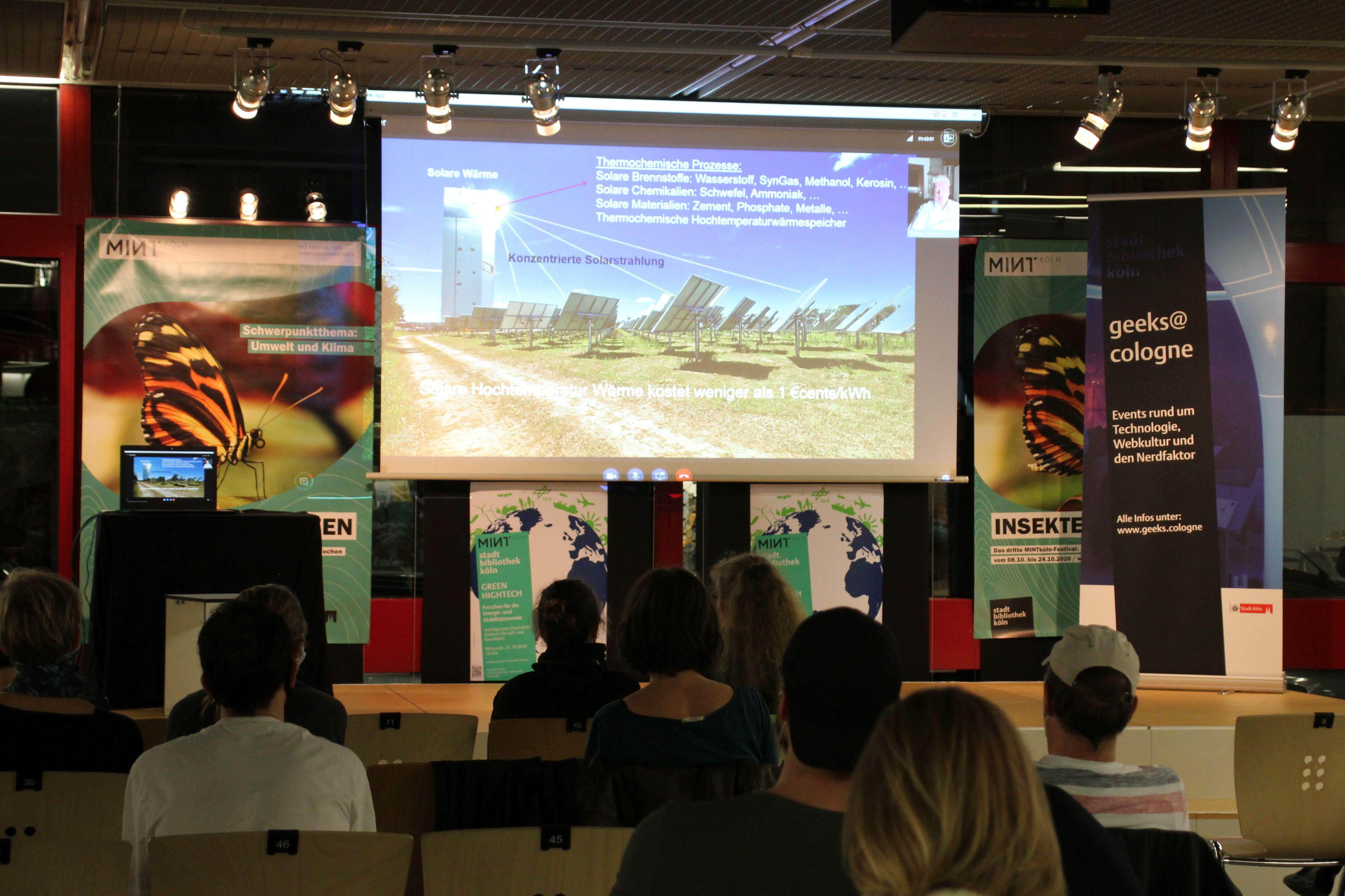Veranstaltungsbühne der Zentralbibliothek. Leinwand mit Vortragsfolie und Live-Bild des Vortragenden. Publikum auf Stühlen im Vordergrund.