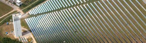 Luftbild von schräg oben: DLR-Solarturm in Jülich mit einem Feld aus über 2000 Spiegeln, die das Sonnenlicht auf den Turm lenken. Drumherum Wiesen und Felder, nur wenig Bebauung.