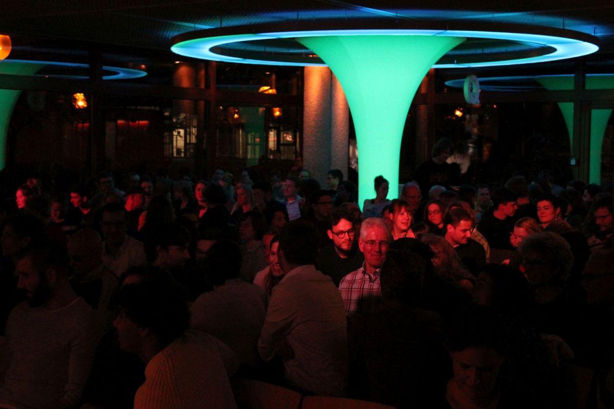 Ins Publikum fotografiert. Der Raum ist dunkel, aber ein großer Lichttrichter leuchtet grün-blau und auf einige Personen im Publikum scheint rotes Licht. Das Publikum diskutiert unterienander.